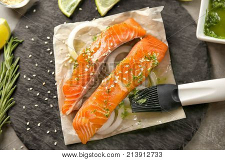 Slate plate with marinated slices of salmon fillet on table