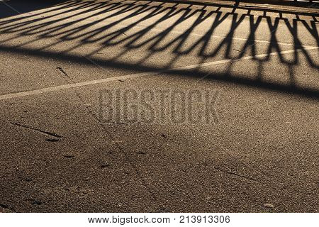 Guardrail Shadow On Icy Asphalt Road Surface. Urban Street Background