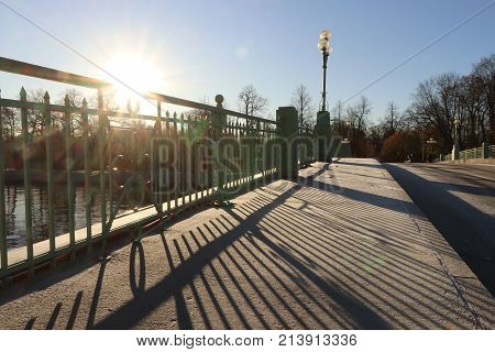 Park Bridge Road With Lantern And Guardrail Sun Lights Shadow. Saint-petersburg.