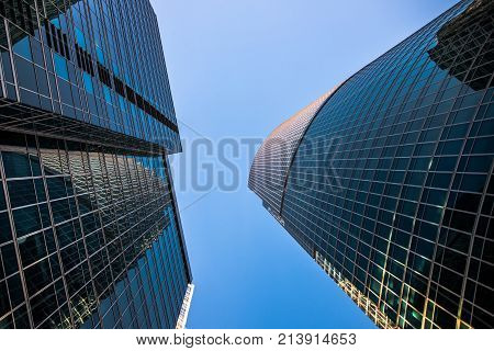 Perspective low angle view of modern glass skyscrapers facades