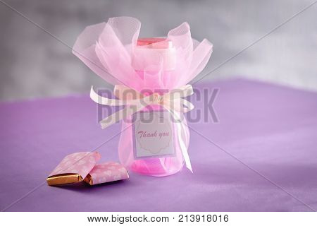 Soap bubble bottle and small chocolates on table