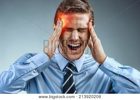 Businessman with pain in his temples. Photo of man suffering from stress or a headache grimacing in pain. Medical concept