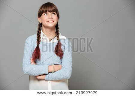 Portrait of a smiling young schoolgirl standing with arms folded and looking away at copy space isolated over gray background