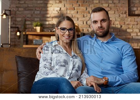 Couple together. Happy young couple sitting on couch at home, smiling.
