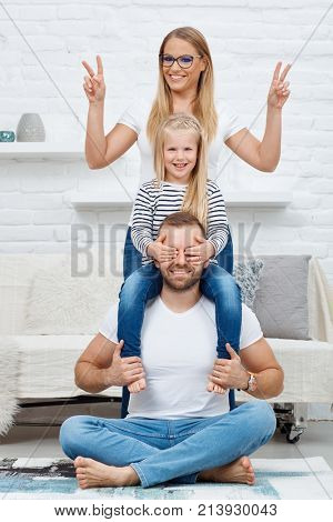 Family portrait. Happy family sitting on floor at home, smiling. Family with one child.
