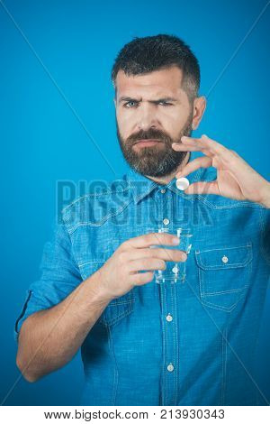 painkiller drug and antidepressant. Health and medicine flu and cold. Treatment hypnotic tablet. Man with beard hold water glass on blue background headache. Hipster drink pill with water illness.