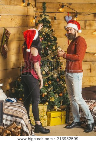 New year guy and girl decorate Christmas tree. Couple in love in santa hat family. Xmas party preparation. Winter holiday and celebration. Christmas man and woman couple at present box.