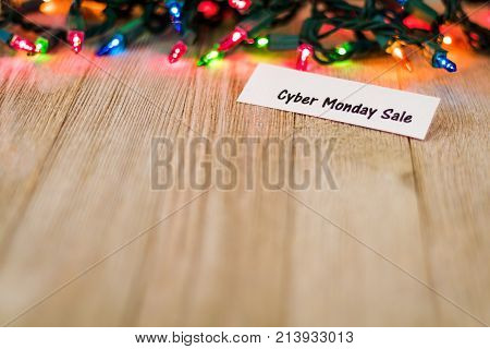 Cyber Monday Sale Concept on wooden board and colored lights, selective focus, room for copy