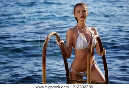 Redhaired woman in bikini relaxed on quiet sea with warm sunset colors.