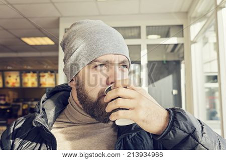 Adult bearded man in a beanie and a dark jacket drinks hot coffee in a cafe