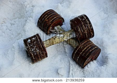 two old dumbbells in white snow on the street