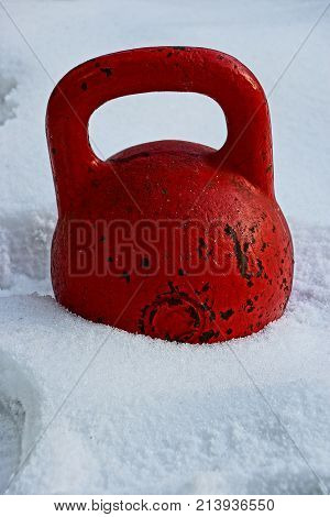 big red old weight in the snow on the street