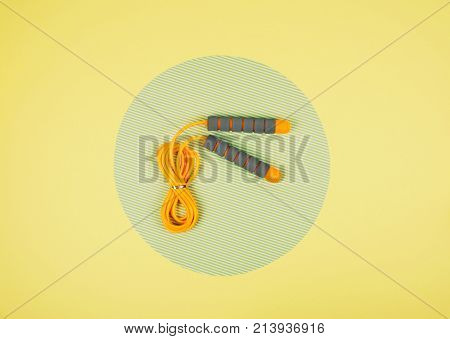 Orange Jump Rope Or Skipping Rope On Yellow And Green Background.
