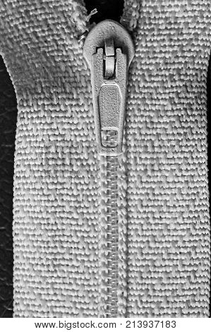 part of a zipper with a lock on white cloth