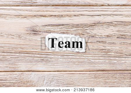 TEAM of the word on paper. concept. Words of TEAM on a wooden background.