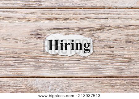 hiring of the word on paper. concept. Words of hiring on a wooden background.