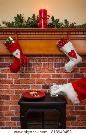 Stockings hanging over a fireplace at Christmas Eve with Santa taking a glass of milk that's been left out for him.