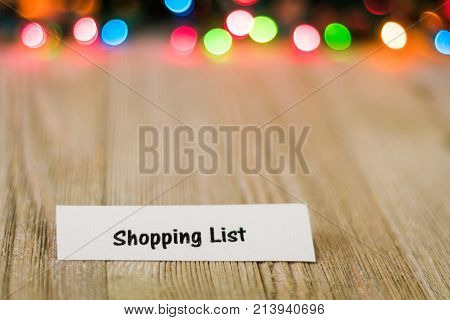 Shopping List Concept on wooden board and colored lights, selective focus, room for copy