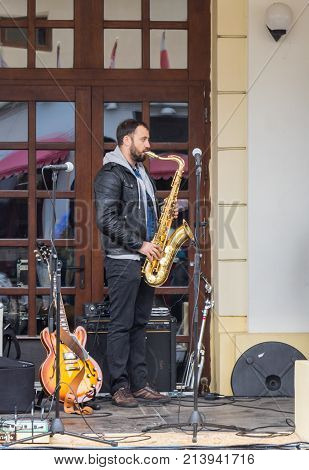 Sibiu Romania October 07 2017 : The musician playing the saxophone performs on the street in front of The State Philharmonics Sibiu - Thalia Concert Hall. Sibiu city in Romania