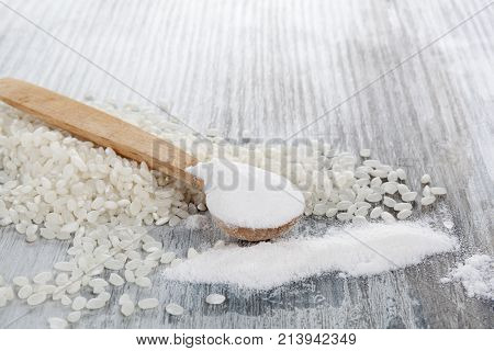 Gluten-free rice flour with rice on wooden table. Celiac disease solution.