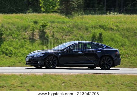 SALO FINLAND - JUNE 3 2016: Black Tesla Model S fully electric car at speed on the road at summer. In-camera panning effect.