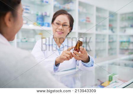 Pharmacist explaining contraindication of medicine to client