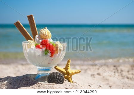 white delicious dessert ice cream multi-colored candy dragee long biscuits lie in glass dessert vase delicious sweet beside yellow starfish and gray round shell stand on yellow sand summer beach
