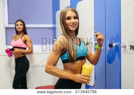 Two young beautiful girls with drinks in their hands shot in a fitness gym cloakroom