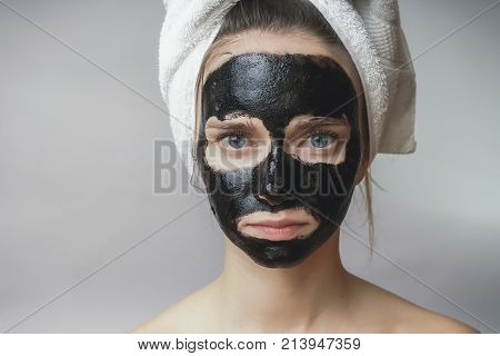 Black mask on woman face ,smiling, skincare ,cleansing pore, against acne