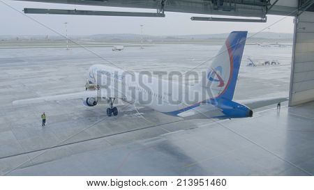 Yekaterinburg, Russia - August 2017: The airplane in the hangar, behind the whole plane and the gangway. Passenger jet airplane white color. Passenger plane in the hangar.