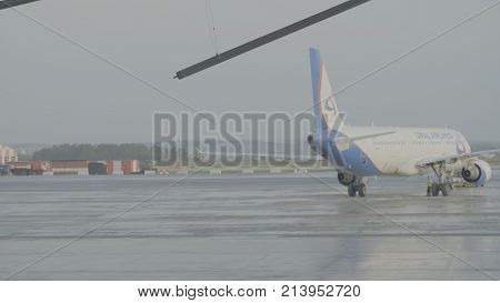 Yekaterinburg, Russia - August 2017: Passenger airplane in front of hangar, preparing for the service of a passenger plane. The airplane in the hangar, behind the whole plane and the gangway