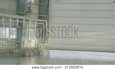 Hangar for aircraft with large open gate at sunny summer day. Gates open aircraft hangar.
