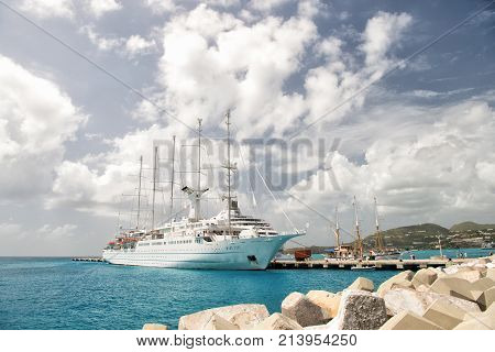 Philipsburg St Maarten - February 13 2016: Ship or sailing yacht in St Maarten at pier on sea or ocean beach on cloudy blue sky. Luxury lifestyle concept. Summer vacation travelling wanderlust