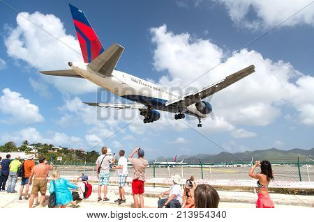 Philipsburg St Maarten - February 13 2016: people watch plane land on island airport on top of maho beach cloudy blue sky. Vacation traveling tourist destination