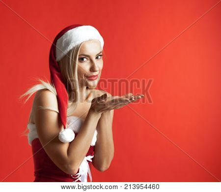 Beautiful santa claus girl blowing kiss on red christmas background