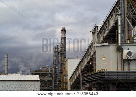 a fragment of some large refinery with a variety of technical designs a distillation column a covered conveyor structure and burning lanterns in the evening
