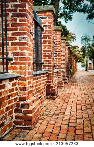 An old red brick wall and sidewalk in a northern Virginia city.
