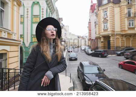 Street portrait of a stylish girl in glasses on the background of the street of the old town. Stylish hip-hop girl poses against the backdrop of a beautiful street.