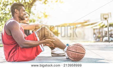 Diverse culture friends sitting on cam after basketball match - People having fun in college campus doing sport - Youth and friendship concept - Warm contrast filter - Focus on black man face