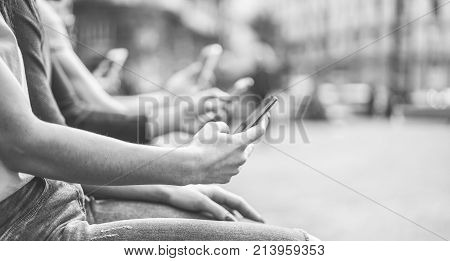 Group of teenagers friends watching mobile phones in city - Young people addiction to technology trends - Alienation moment for new generation problem - Focus on first hand - Vintage retro filter