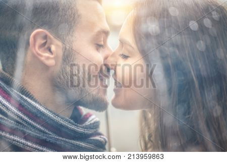 Close up of young couple in love kissing after rain under transparent umbrella - Handsome man and woman enjoying first date at sunset - Tender moments and love relationship concept - Focus on girl eye