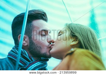 Young couple kissing under transparent umbrella - Girlfriend and boyfriend having tender moments - Tender moments and love concept - Focus on man eye - Radial blue and green filters editing