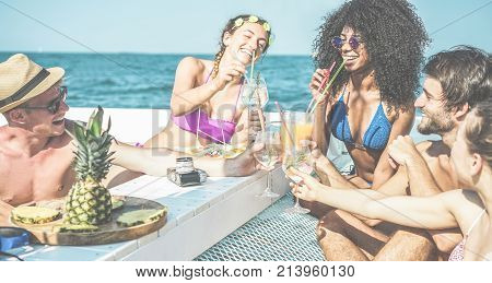 Happy friends drinking tropical cocktails at boat party and eating pineapple - Young people having fun in sea exclusive excursion - Youth friendship and summer concept - Main focus on afro woman face