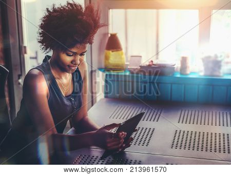 Cute African American student girl is checking e-mail using digital tablet while sitting at the table in dar settings of verandah in her summer house during vacations with copy space place for message