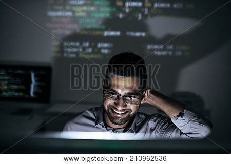 Smiling software developer looking on script on computer screen