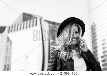 Girl in fashionable leather jacket with cell phone. Beauty look and urban fashion. communication business and new technology. Fashion model pose smiling. woman with happy face in hat speak on phone.