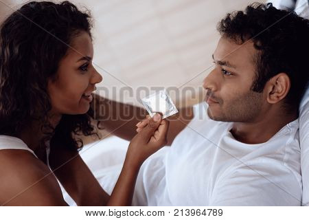 Black man and woman in the bedroom. A woman lies in bed over a man and suggests that he use a condom. The man lies and looks at the woman.