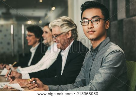 Confident young Asian manager sitting at table and looking at camera. He holding pen and paper. His colleagues sitting in row behind him. Meeting concept