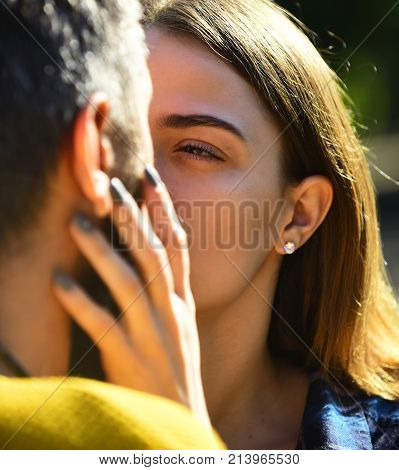 Man and woman with sincere sight on sunny outside background. Tenderness love and dating concept. Girl and guy or happy lovers on a date hug and cuddle. Couple in love is going to kiss