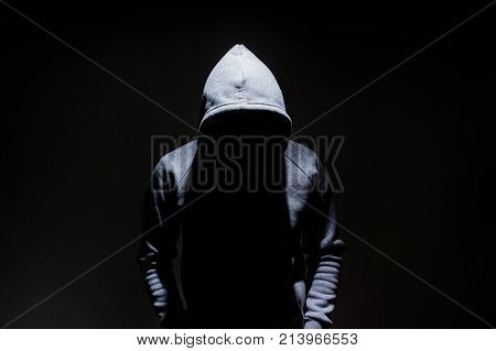 Silhouette of man in the hood dark mysterious man hoodie murderer hacker anonymus on the black background with free space